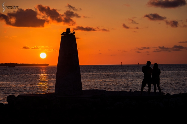Sunset across the bay - silhouette of the beacon and a couple