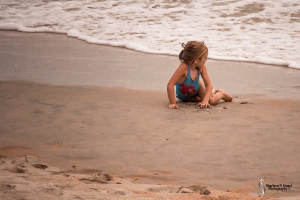 Little girl playing in the waves