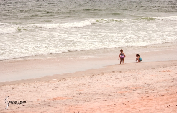 Two little girls playing on the beach