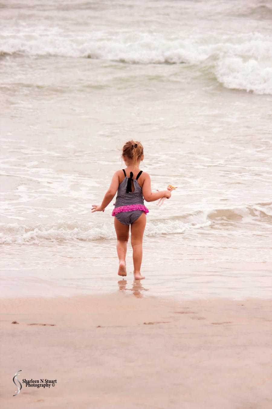 Little girl running into the waves